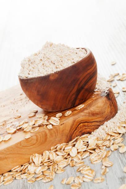 harina de avena en bol de madera
